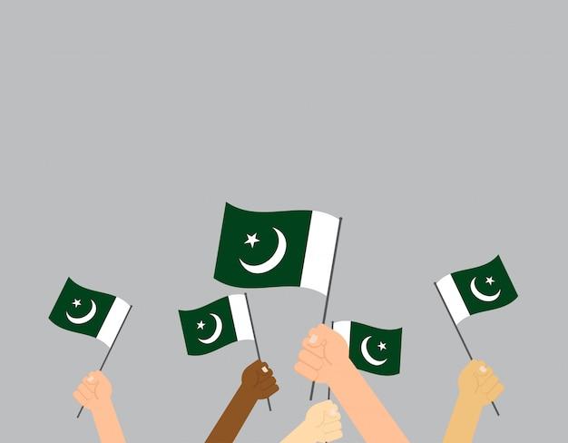Mains tenant le drapeau du pakistan