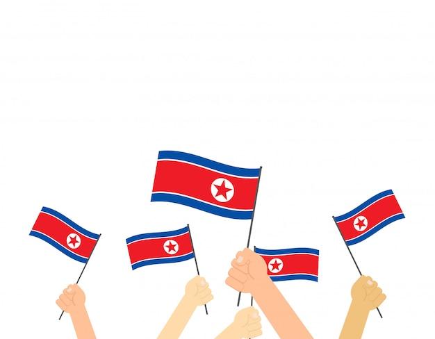 Mains tenant des drapeaux de la corée du nord
