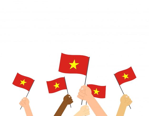 Mains tenant des drapeaux du vietnam