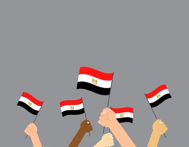Mains tenant des drapeaux d'egypte