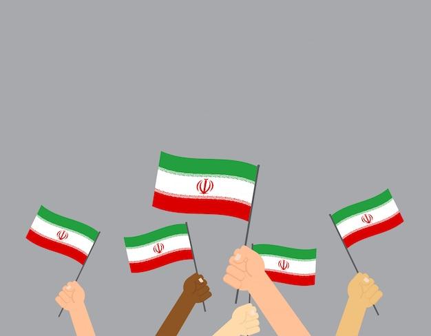 Mains tenant des drapeaux iraniens