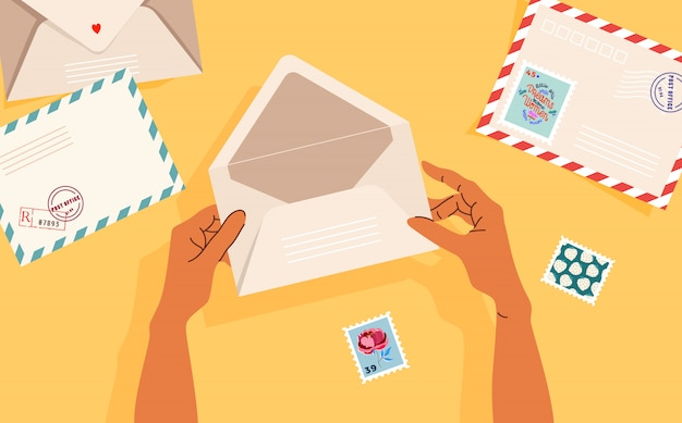 Mains tenant une enveloppe ouverte. enveloppes, timbres et cartes postales sur la table. vue de haut en bas. bannière illustrée moderne, conception de cartes. concept de correspondance et de livraison postale.