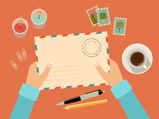 Mains tenant l'enveloppe avec des timbres. papeterie. vue de dessus. envoi d'une lettre écrite via le service postal