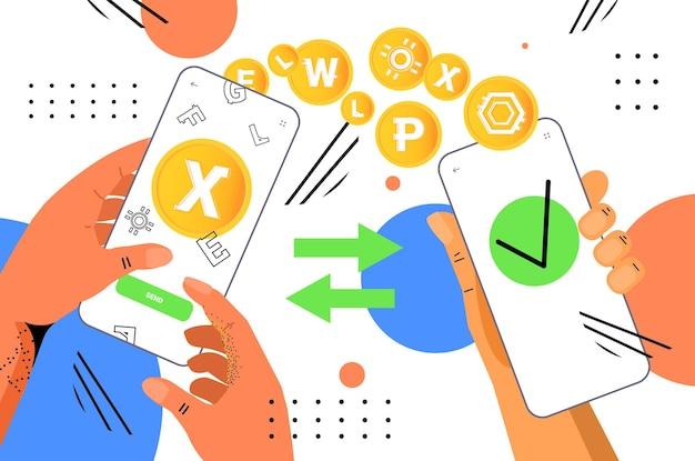 Mains tenant des smartphones envoyant et recevant des pièces numériques exploitant une transaction bancaire d'échange de crypto-monnaie