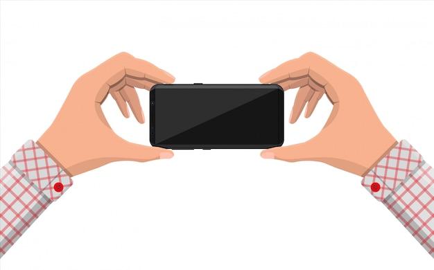 Les mains tiennent le téléphone mobile.