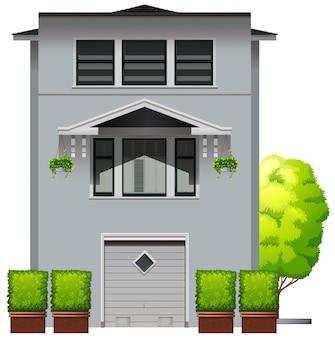 Maison grise avec des plantes et des arbres