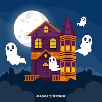 Maison hantée d'halloween avec des fantômes sur un design plat