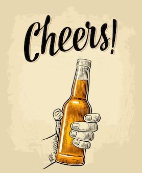 Mâle main tenant une bouteille ouverte de bière pleine