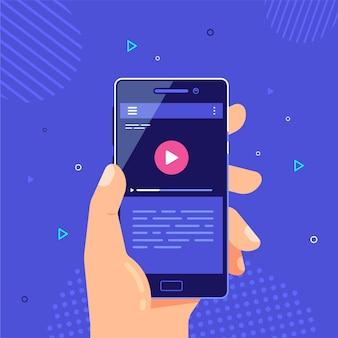 Mâle main tenant un téléphone portable avec lecteur vidéo sur l'écran. application vidéo mobile. streaming vidéo sur téléphone.