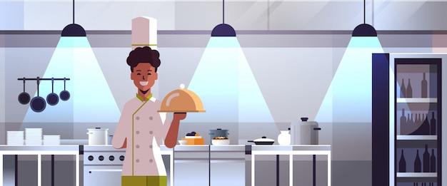 Mâle professionnel chef cuisinier tenant couvert plateau servant plateau afro-américain homme en uniforme cuisson concept alimentaire moderne restaurant cuisine intérieur portrait