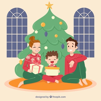 Maman, papa et fils assis sous le sapin de noël