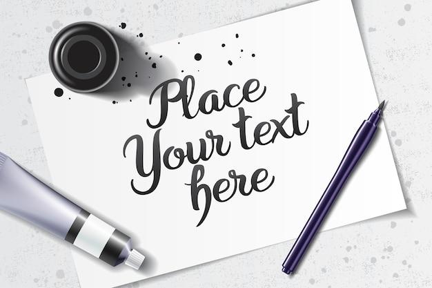 Maquette de calligraphie avec stylo pinceau et bouteille d'encre noire sur l'espace d'une feuille de papier blanc et table grunge
