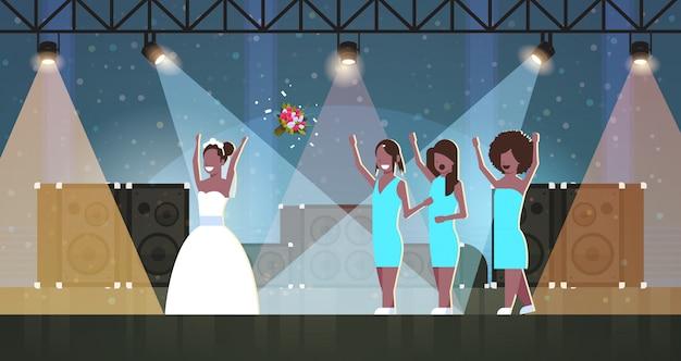 Mariée en robe blanche jetant un bouquet pour les demoiselles d'honneur pour attraper les filles s'amusant sur les lumières de la scène effets studio disco concept de jour de mariage pleine longueur horizontale