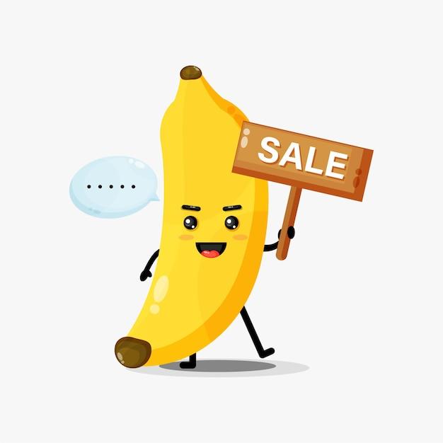 Mascotte de banane mignonne avec un signe de vente