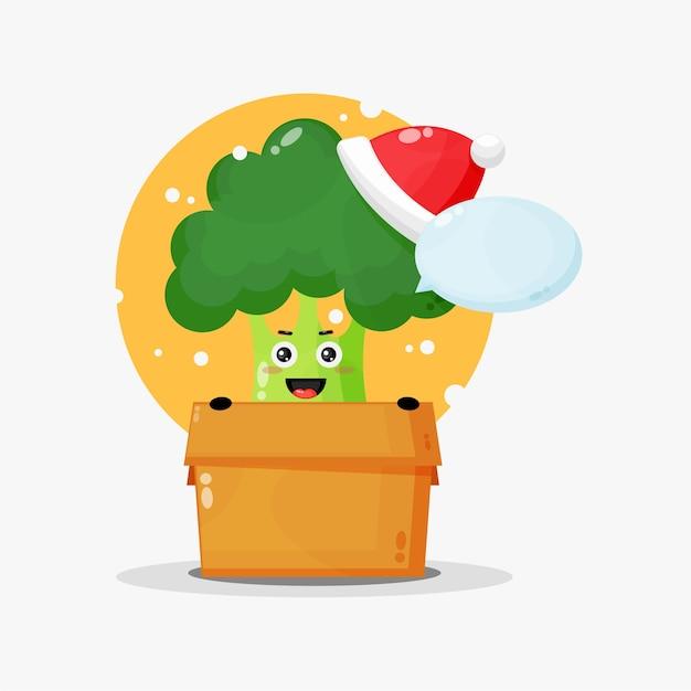 Mascotte de brocoli mignon dans une boîte portant un chapeau de noël