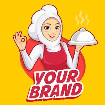 La mascotte d'une femme chef portant un tablier rouge avec des doigts ok.