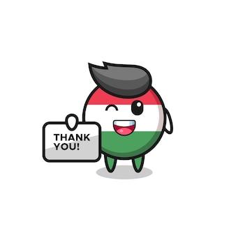La mascotte de l'insigne du drapeau hongrois tenant une bannière qui dit merci, design de style mignon pour t-shirt, autocollant, élément de logo