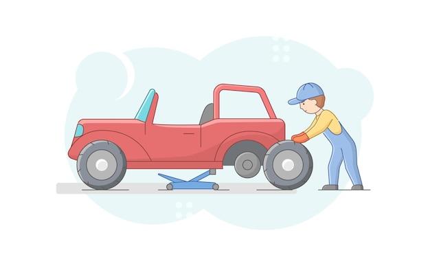 Mécanicien en uniforme change de pneus sur un véhicule rétro à l'aide d'outils et d'ascenseur de voiture