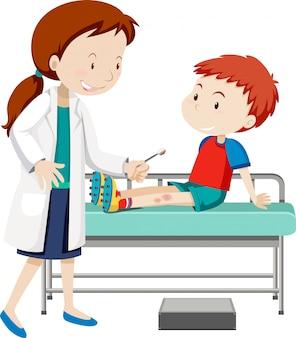Médecin aidant le jeune garçon avec une jambe endolorie