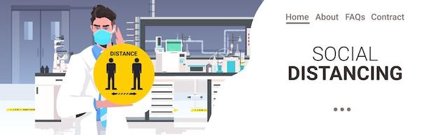 Médecin en masque tenant signe rond jaune distance sociale prévention de la pandémie de coronavirus hôpital laboratoire intérieur copie espace portrait horizontal