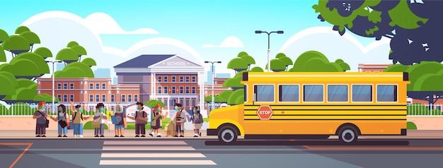 Mélanger des écoliers de race portant des masques pour empêcher les élèves de la pandémie de coronavirus de se tenir ensemble près du bus scolaire