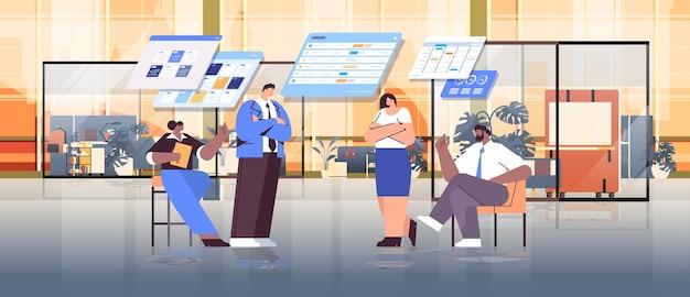 Mélanger l'équipe d'hommes d'affaires de course analysant des données statistiques sur des tableaux virtuels un travail d'équipe réussi