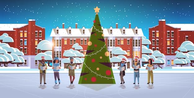 Mélanger les gens de course de lecture de livres joyeux noël vacances célébration concept hommes femmes portant des chapeaux de père noël debout près de l'arbre en forme de vecteur de paysage urbain moderne je