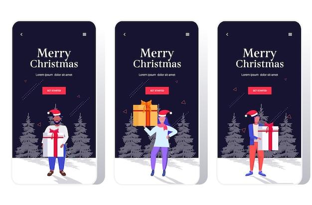 Mélanger les gens de race en bonnet de noel tenant boîte cadeau cadeau joyeux noël bonne année vacances célébration