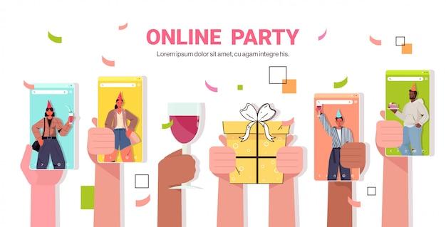 Mélanger les gens de race dans les écrans de smartphone pour célébrer la fête d'anniversaire en ligne lors d'un appel vidéo