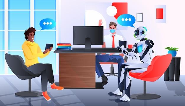 Mélanger des hommes d'affaires de course dans des masques discutant avec un robot au bureau technologie d'intelligence artificielle concept de pandémie de coronavirus