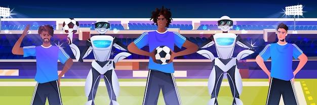 Mélanger des hommes de course et des robots joueurs de football avec des ballons de football debout sur le stade de concept de technologie d'intelligence artificielle portrait horizontal