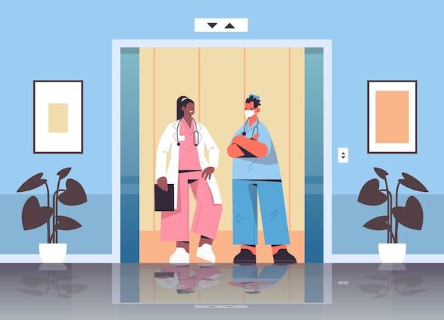 Mélanger les travailleurs médicaux de race discuter lors de la réunion dans l'ascenseur de l'hôpital médecine de santé médecine concept médecins en uniforme horizontal