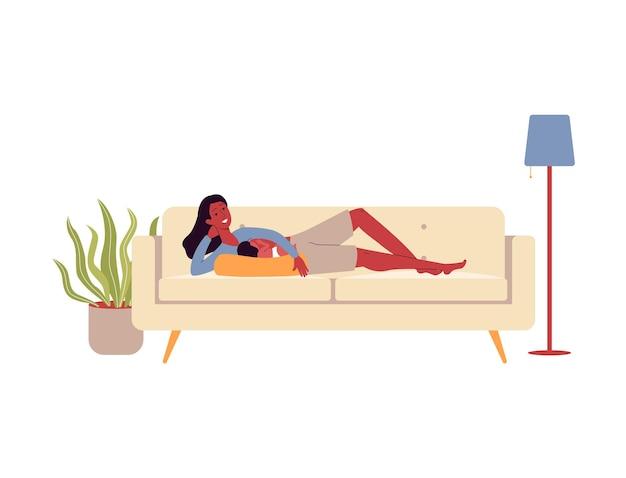 Mère allaitant bébé couché dans le canapé du salon et souriant
