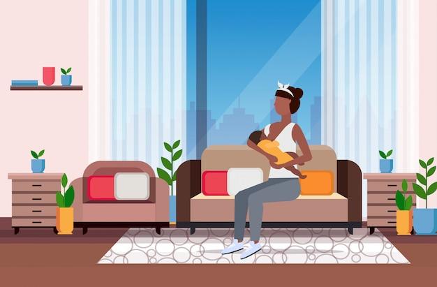 Mère allaitant son bébé nouveau-né femme assise sur un canapé avec petit enfant maternité nutrition lactation concept moderne salon intérieur plat pleine longueur