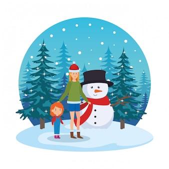 Mère et fille avec bonhomme de neige dans la neige