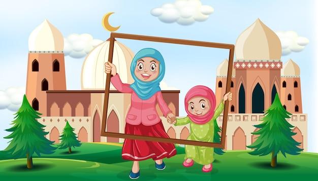 Mère et fille tenant un cadre photo en plein air