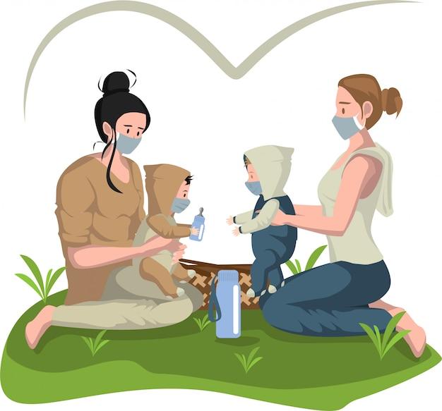 La mère joue avec leurs bébés pendant un pique-nique à l'extérieur