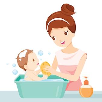 Mère lave bébé dans une petite baignoire