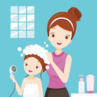 Mère laver les cheveux fille dans la salle de bain