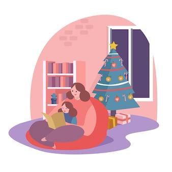 Une mère lit un livre pour sa fille à côté d'un sapin de noël