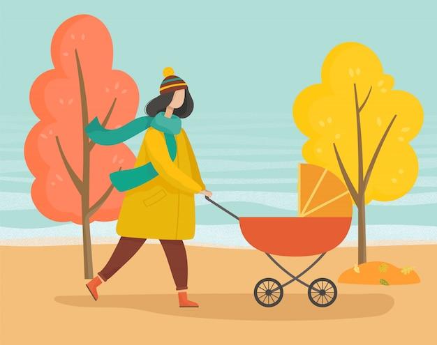 Mère marchant avec bébé dans un landau dans un parc d'automne