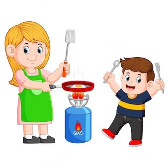 Mère et son fils cuisant un oeuf avec une friture