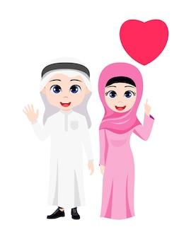 Mignon beau garçon arabe garçon et fille couple debout et en agitant et pointant vers la forme de coeur avec une robe traditionnelle isolée