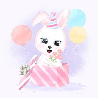 Mignon bébé lapin dans une boîte cadeau et des ballons