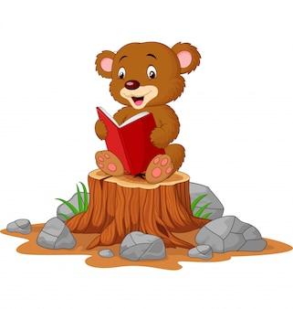 Mignon bébé ours livre de lecture sur une souche d'arbre