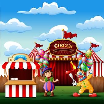 Mignon un clown et une fille à l'entrée du cirque