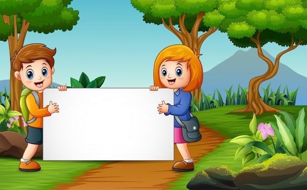 Mignon un écoliers tenant un tableau blanc sur la nature