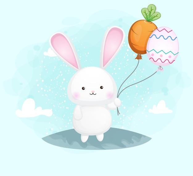 Mignon lapin souriant heureux tenant le ballon de carotte et le ballon d'oeuf
