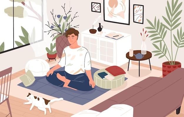 Mignon mec ou garçon assis les jambes croisées dans sa chambre ou son appartement et pratiquant le yoga