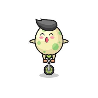 Le mignon personnage d'oeuf tacheté fait du vélo de cirque, un design de style mignon pour un t-shirt, un autocollant, un élément de logo
